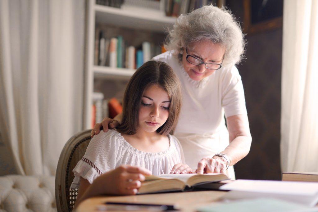 grandmother helping child read